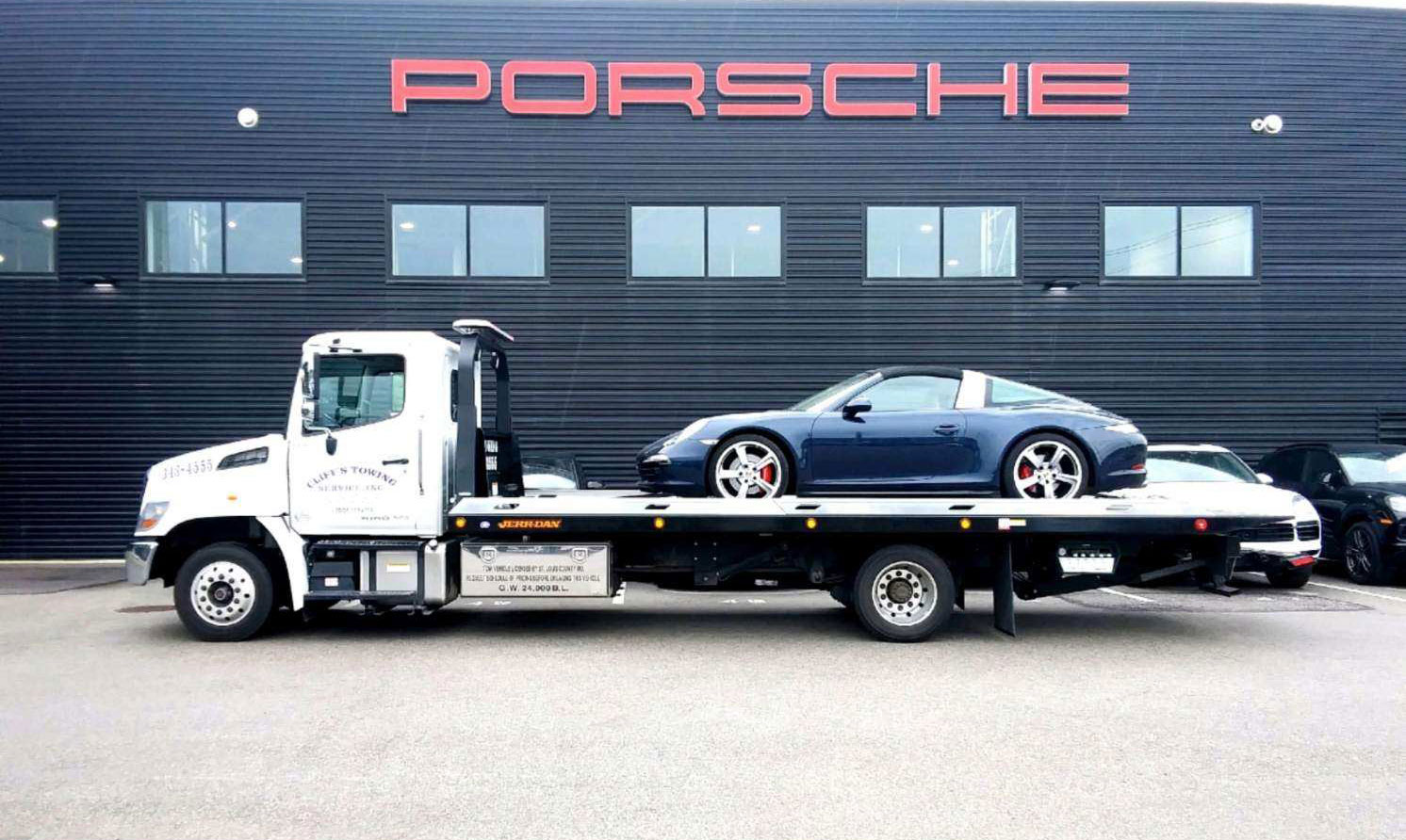 Cliff's Towing Service flat bed truck with 911 Porsche on it in front of St. Louis Porsche dealership